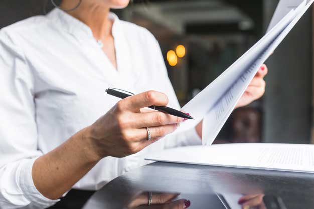 close-up-woman-examining-document